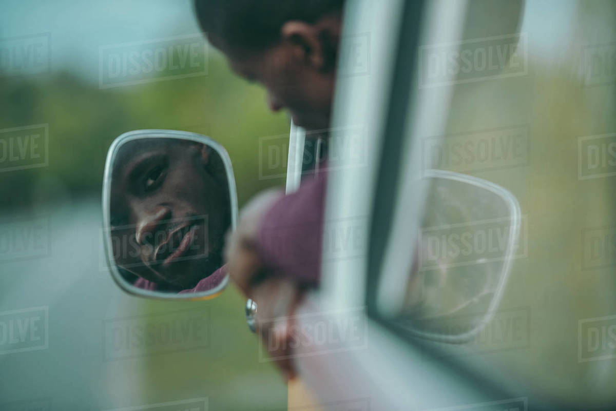 Handsome young African American man looking in mirror in retro minivan Royalty-free stock photo