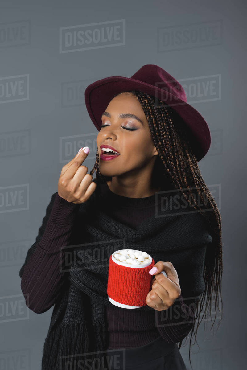 Smiling stylish African American girl holding cup with hot drink and eating  marshmallows stock photo