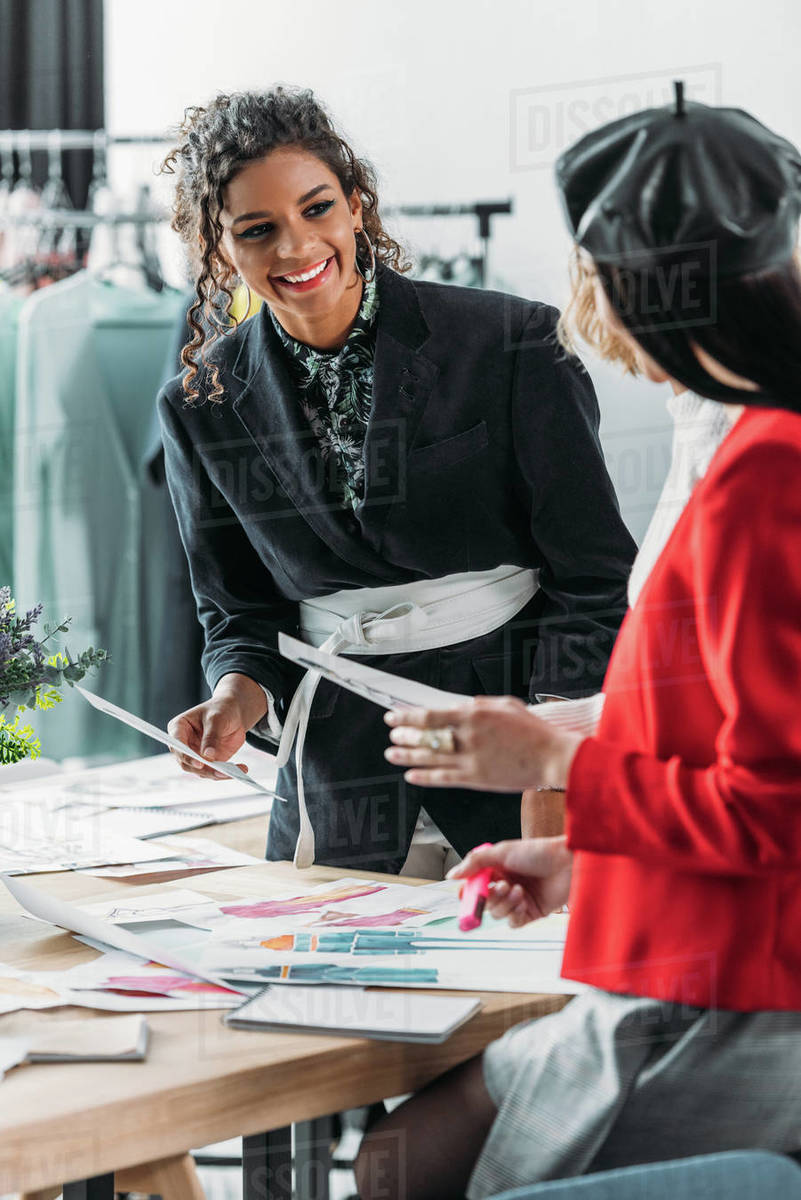 Young Smiling African American Fashion Designer Looking At Colleagues While Working With Sketches Stock Photo Dissolve