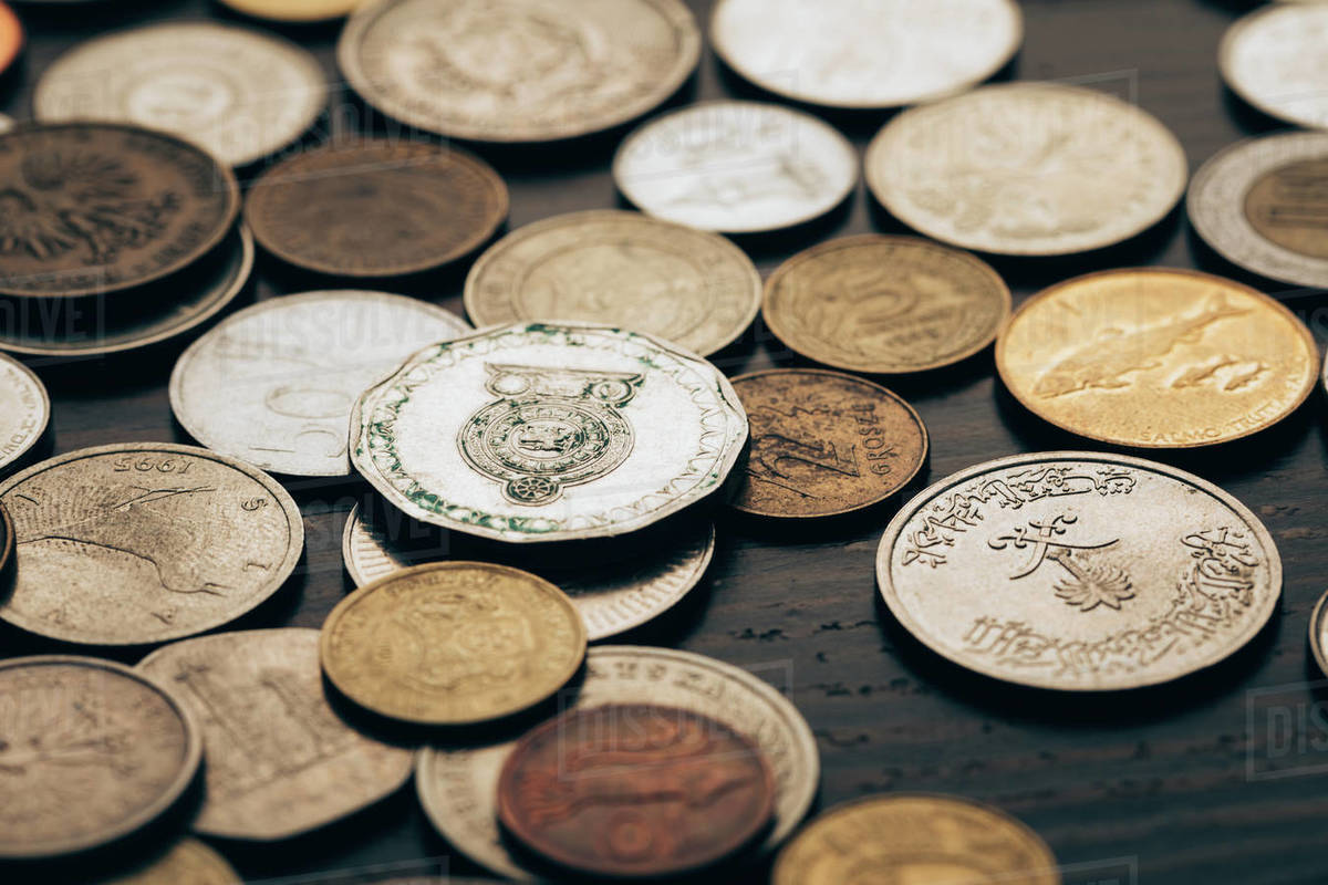 Close up of collection of coins on wooden tabletop stock photo