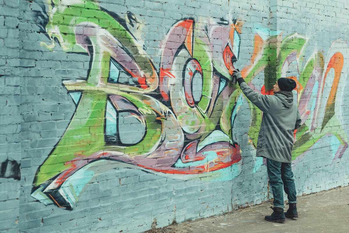 Street Artist Painting Colorful Graffiti On Wall Stock Photo