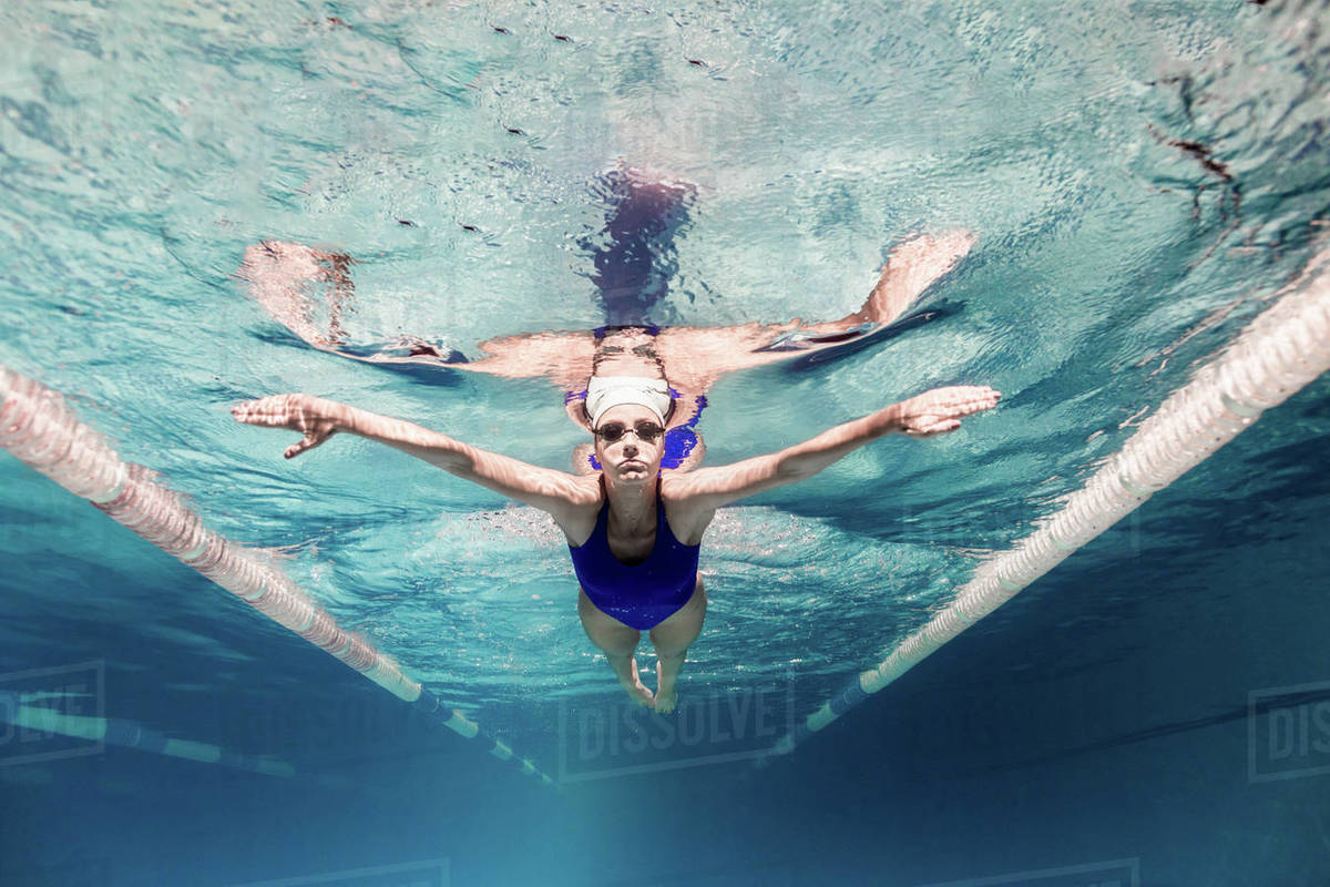 Underwater picture of female swimmer in swimming suit and goggles training  in swimming pool stock photo