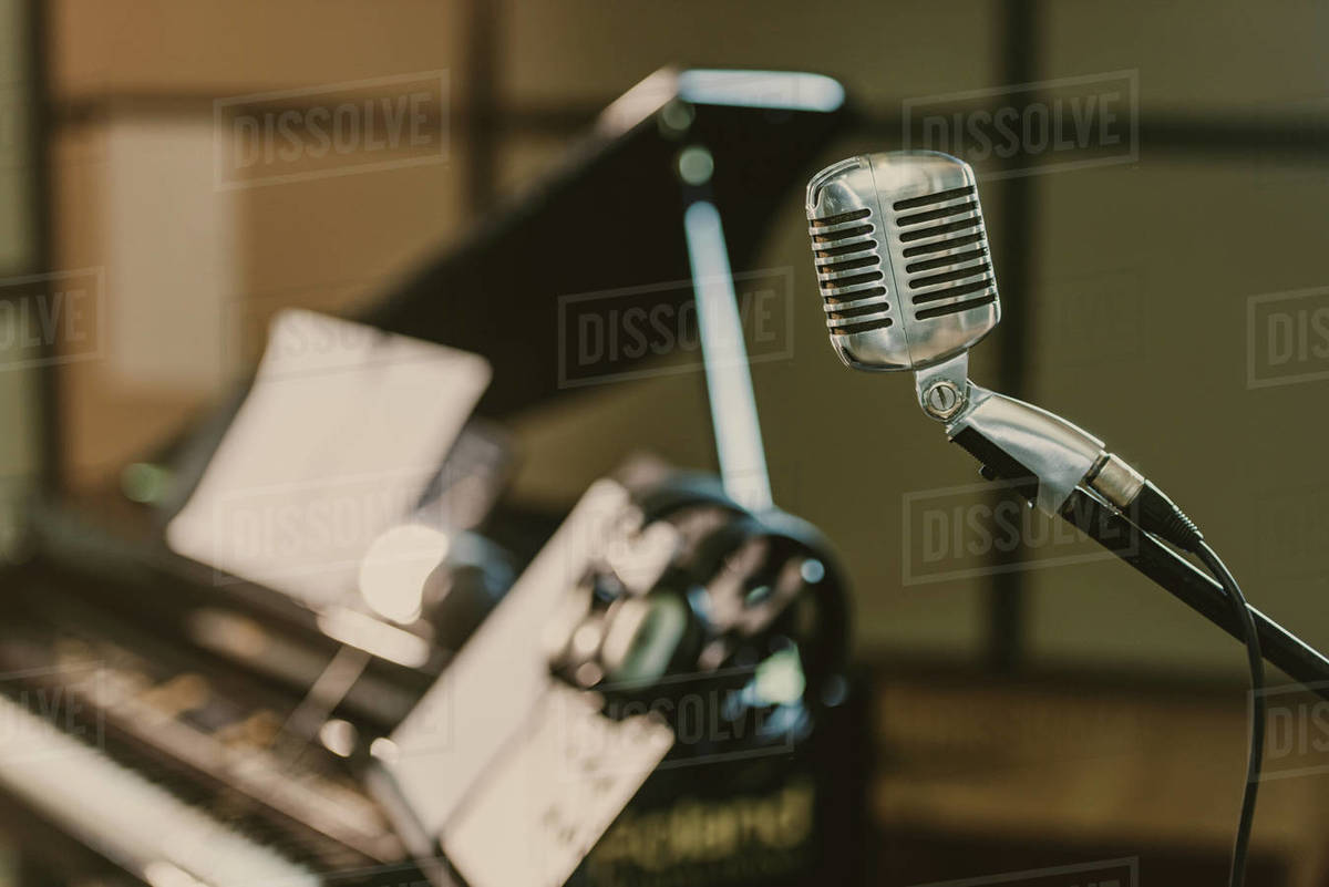 close,up shot of vintage microphone in front of blurred piano D2115_253_991