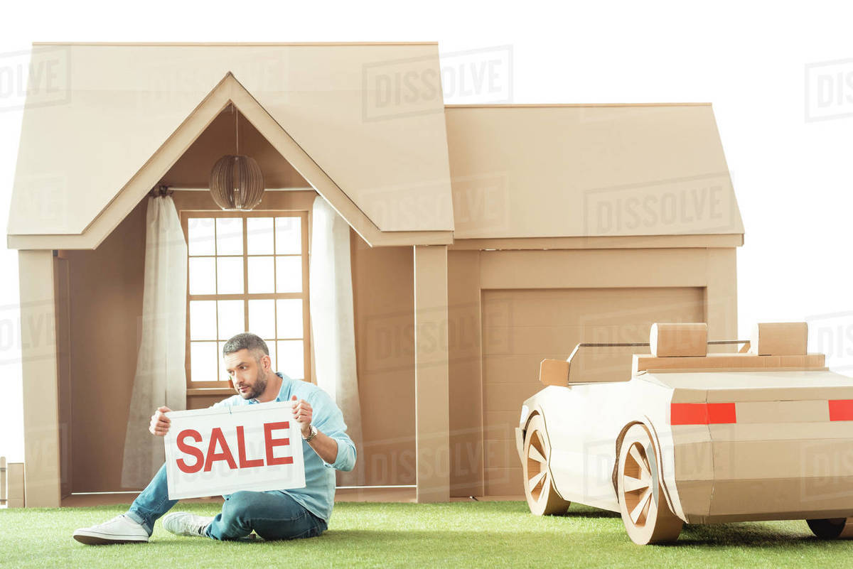 Man holding sale signboard in front of cardboard house isolated on white  stock photo