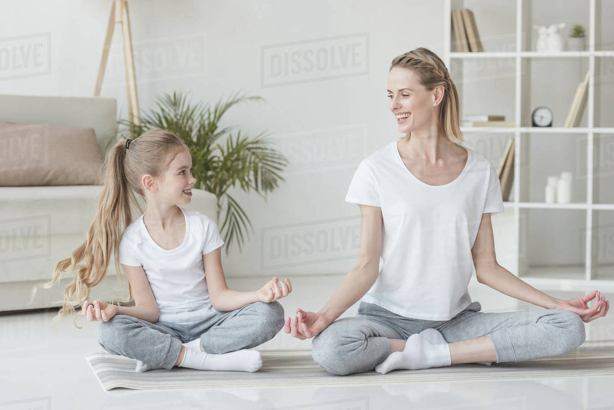Happy mother and daughter sitting in lotus pose at home together Royalty-free stock photo