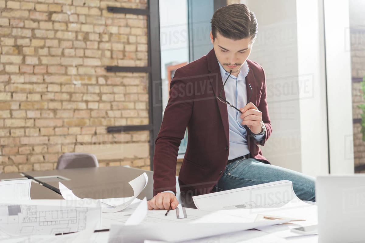 Thoughtful young architect sitting on work table with building plans at office Royalty-free stock photo