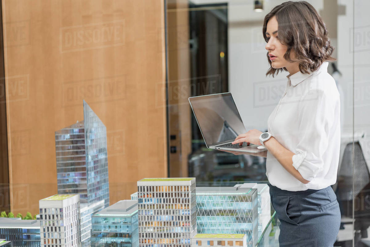 Beautiful young architect using laptop near building models Royalty-free stock photo
