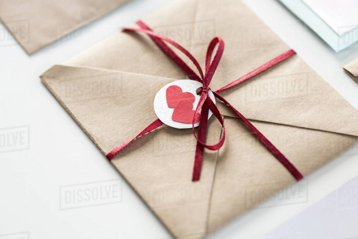 envelope with tag with two hearts and ribbon isolated on white, wedding invitation card design concept Royalty-free stock photo