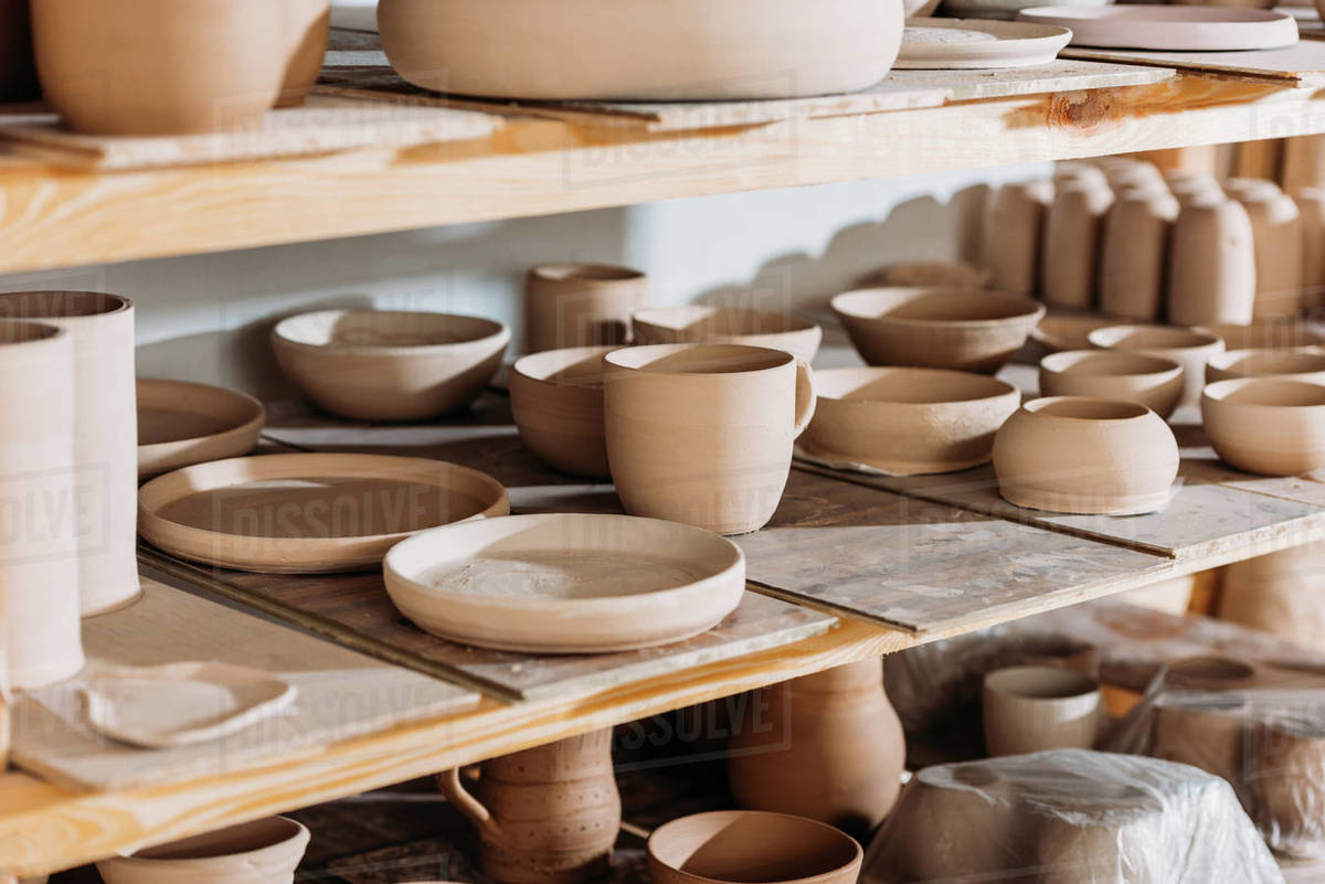 Ceramic Plates And Bowls On Wooden Shelves In Pottery Workshop Stock Photo Dissolve