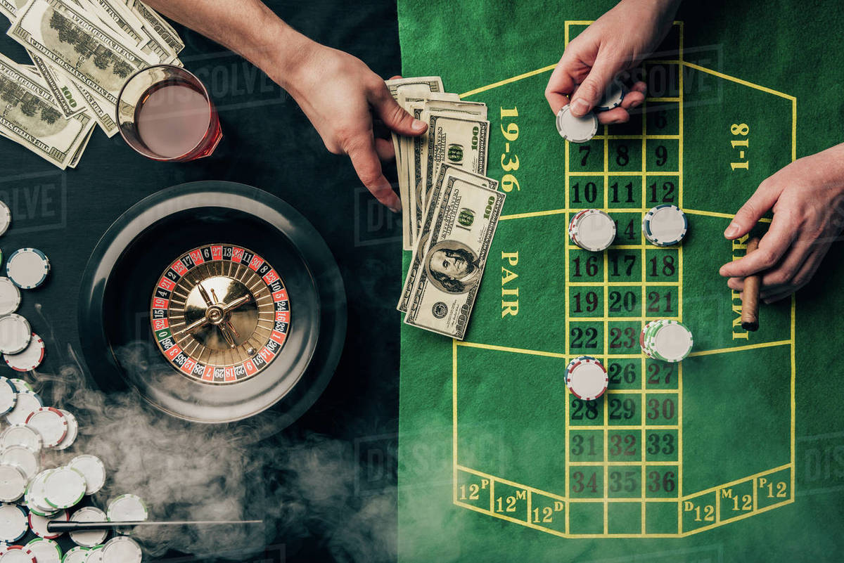 Men Placing A Bet On Casino Table With Roulette Stock Photo
