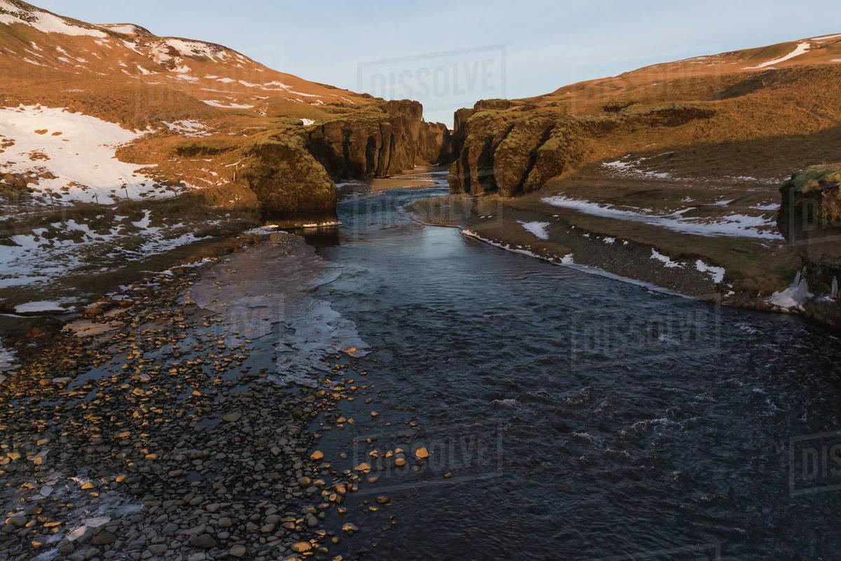 Beautiful Icelandic landscape with cold river, rocks and snow,  fjadrargljufur, Iceland stock photo