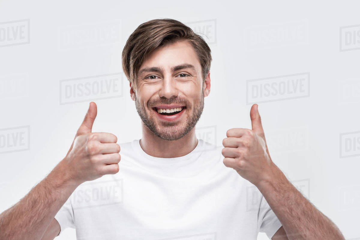 Handsome smiling man showing thumbs up, isolated on white - Stock Photo -  Dissolve