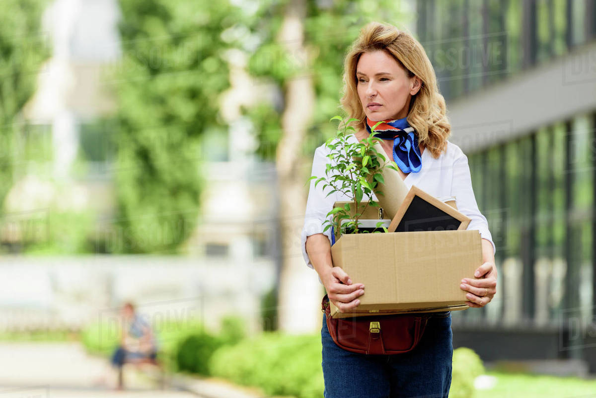 Attractive woman holding paper box with office stuff on street ...