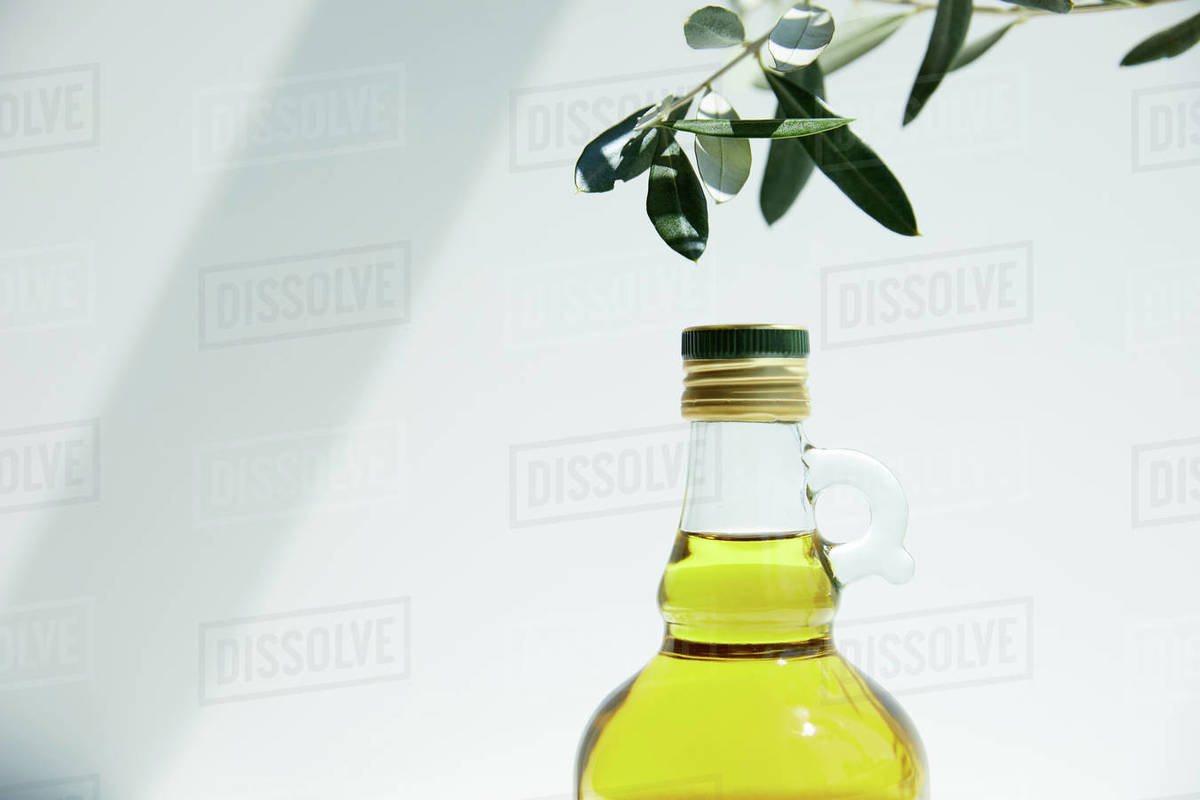 Bottle Of Aromatic Olive Oil And Branch On White Background Stock Photo