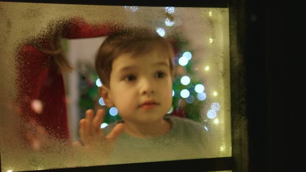 d1bff20d0 Adorable little boy and girl looking through the window and admiring first  snow flakes and fireworks on christmas evening. stock footage