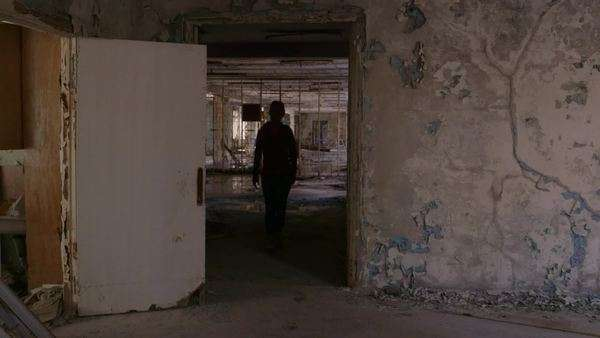 Long shot of woman walking through abandoned passageway Rights-managed stock video
