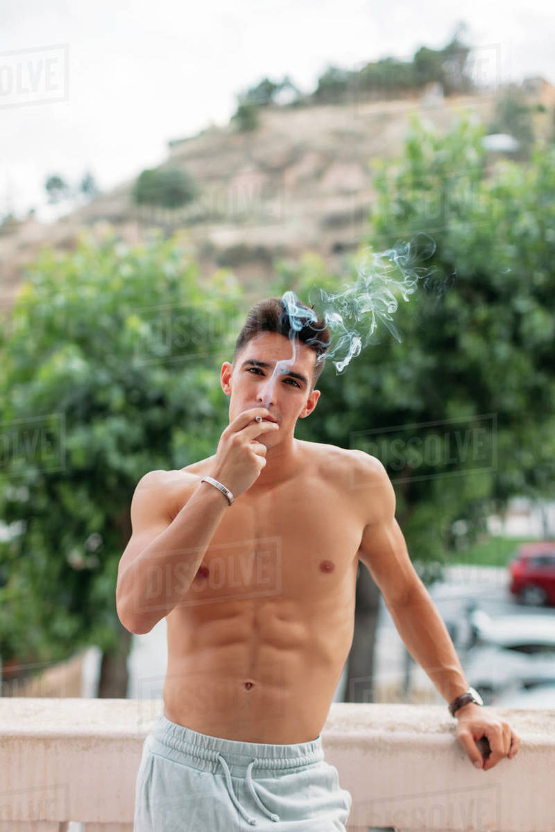 Portrait of shirtless young man smoking on balcony, Lleida, Spain Royalty-free stock photo