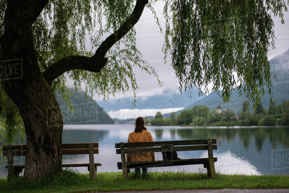 Woman sitting on the bench under tree and looking at lake in mountains Royalty-free stock photo