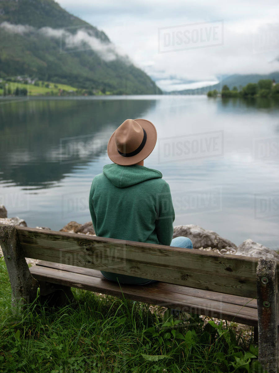Man in hat sitting and looking at view of mountain lake in fog Royalty-free stock photo