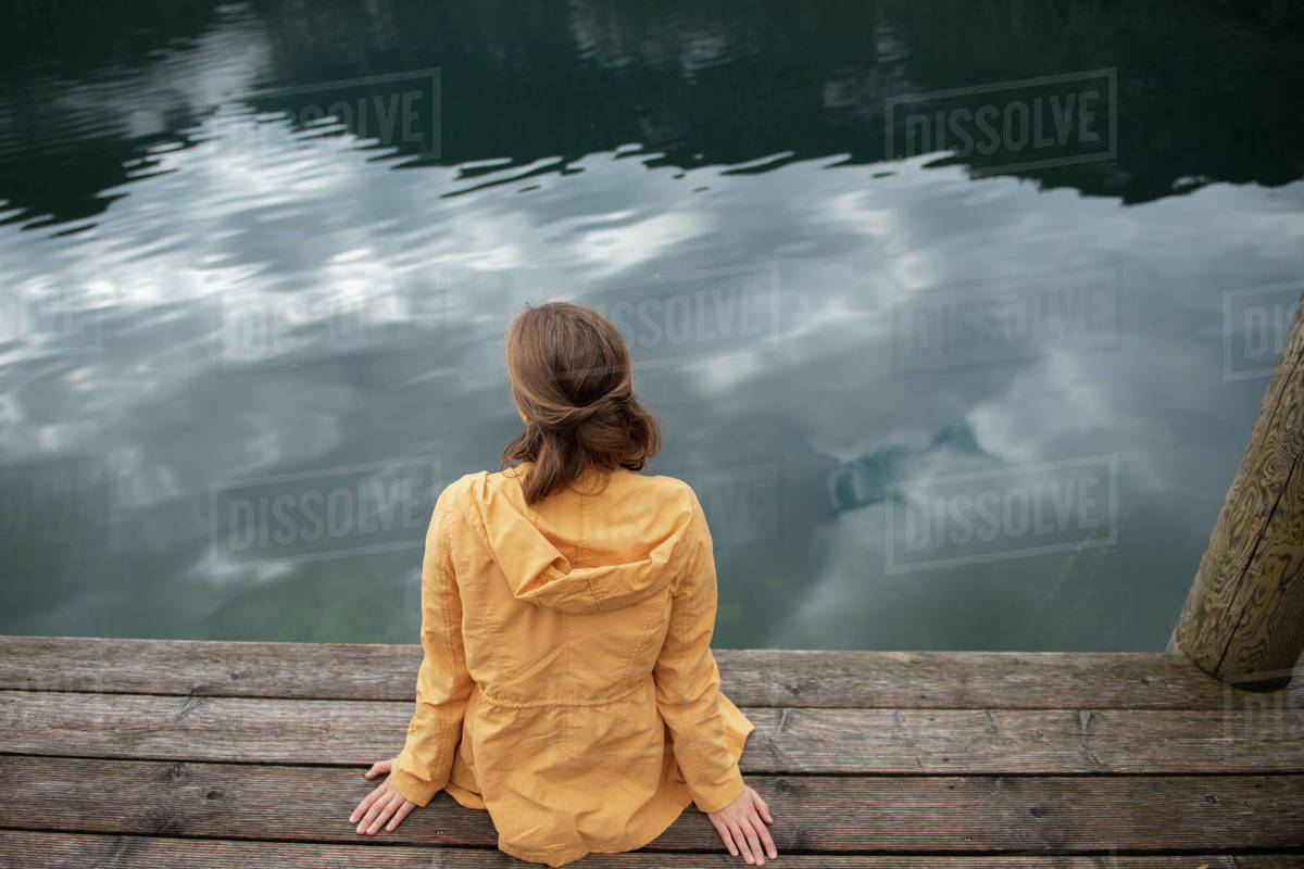 Back view of woman sitting on wooden pier at lake shore and looking at water Royalty-free stock photo