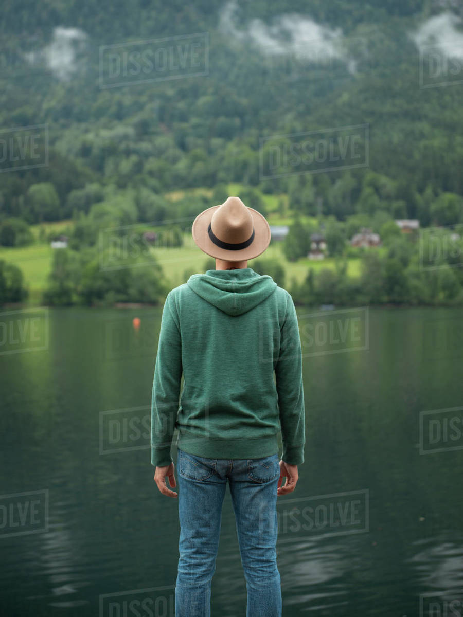 Back view of man standing at lake shore and enjoying the lake view Royalty-free stock photo