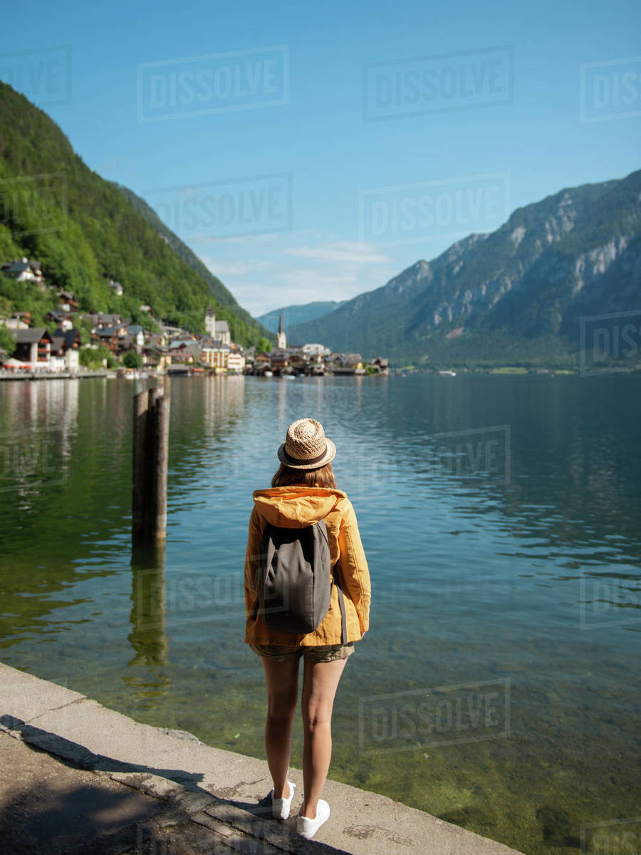 Female tourist standing at lake shore and enjoying the view Royalty-free stock photo