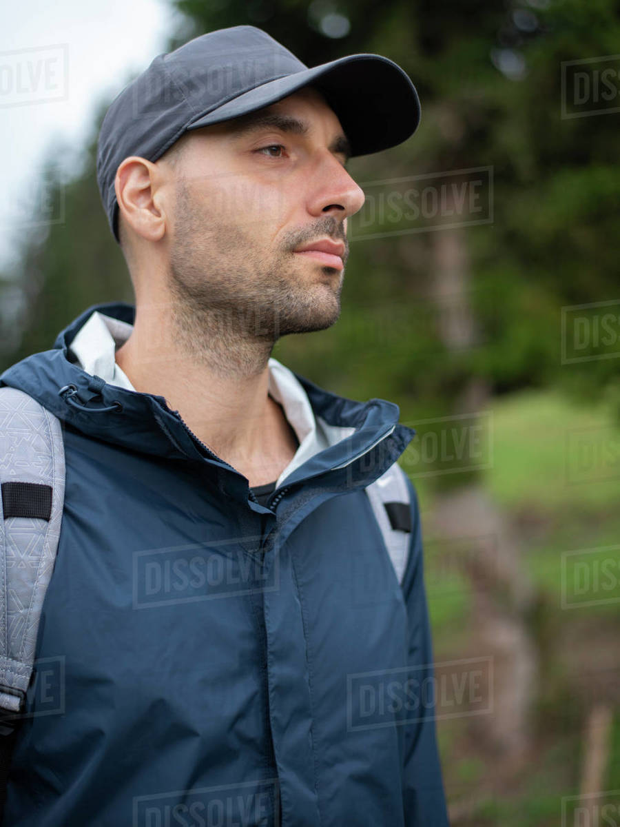 Man with backpack standing in forest and looking far distance Royalty-free stock photo