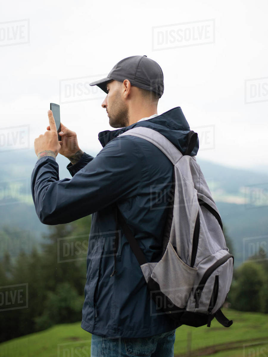 Man with backpack photographing by smart phone in forested mountains Royalty-free stock photo
