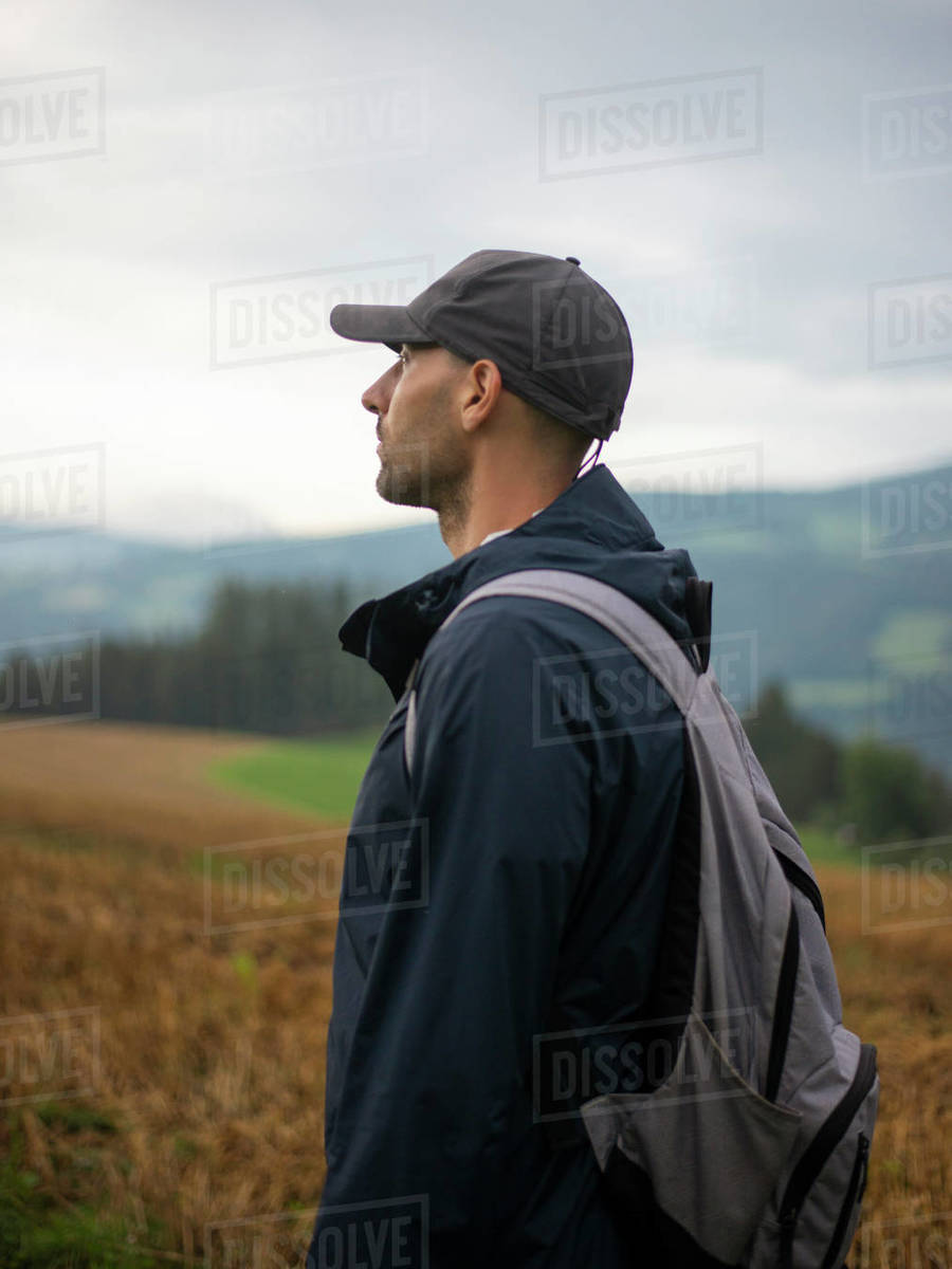Male backpacker standing in field and looking away against cloudy sky and forested mountains Royalty-free stock photo