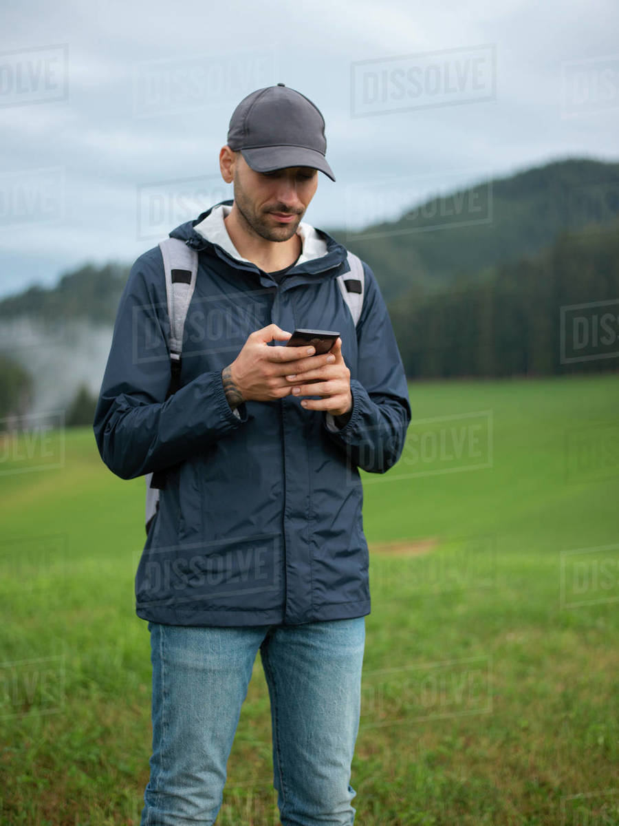 Man using mobile phone while standing in field  Royalty-free stock photo
