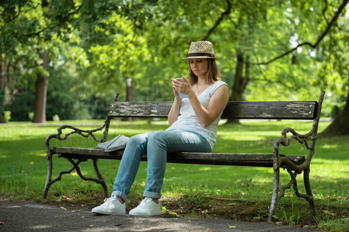 Woman sitting on bench in park texting on cell phone Royalty-free stock photo