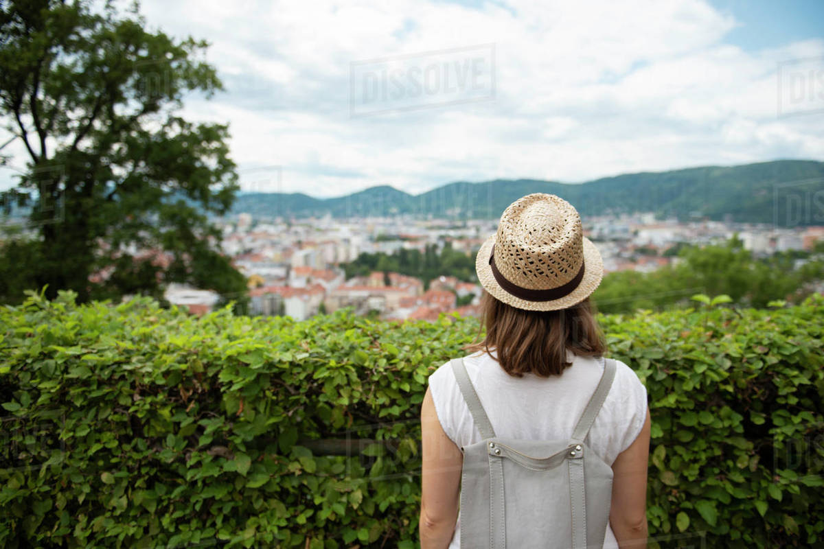 Back view of female tourist looking at cityscape through foliage Royalty-free stock photo