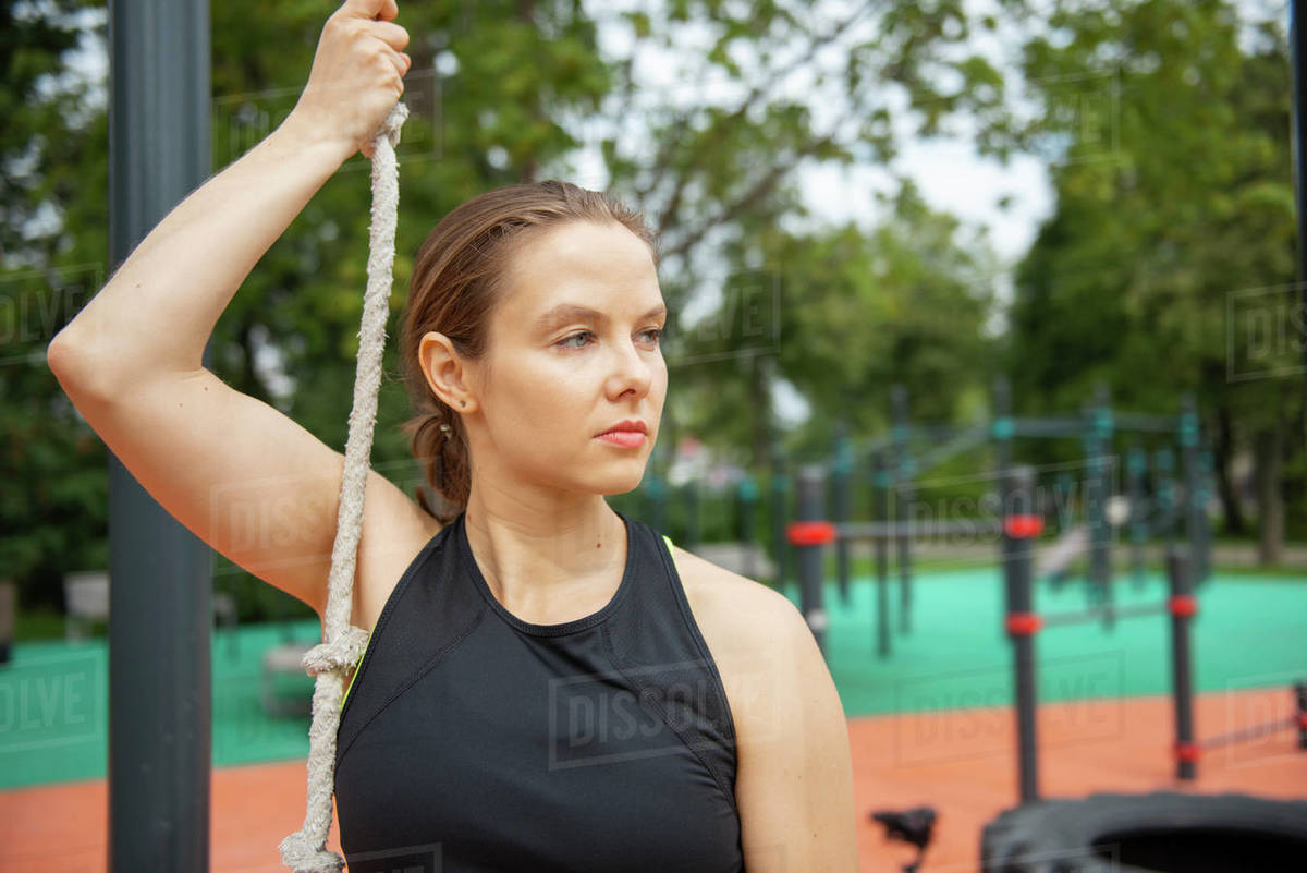 Woman holding rope while standing outdoors and relaxing after workout  Royalty-free stock photo