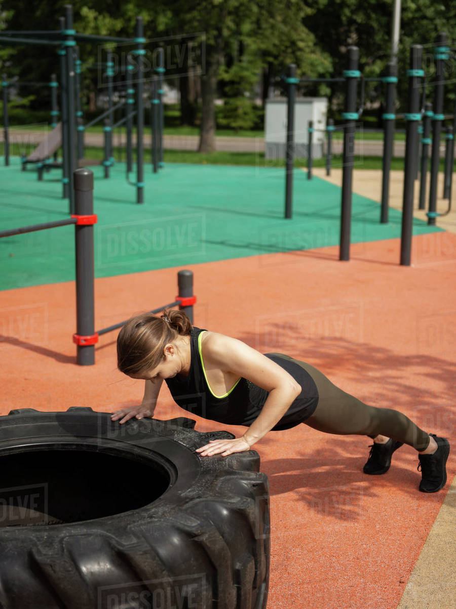 Athletic woman exercising with a big tire doing push-ups outdoors Royalty-free stock photo