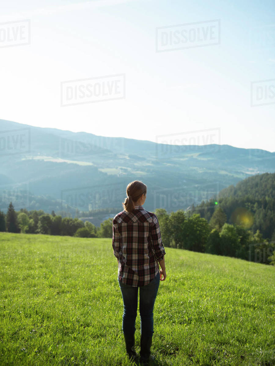 Woman standing on the hill in grass field during sunrise Royalty-free stock photo