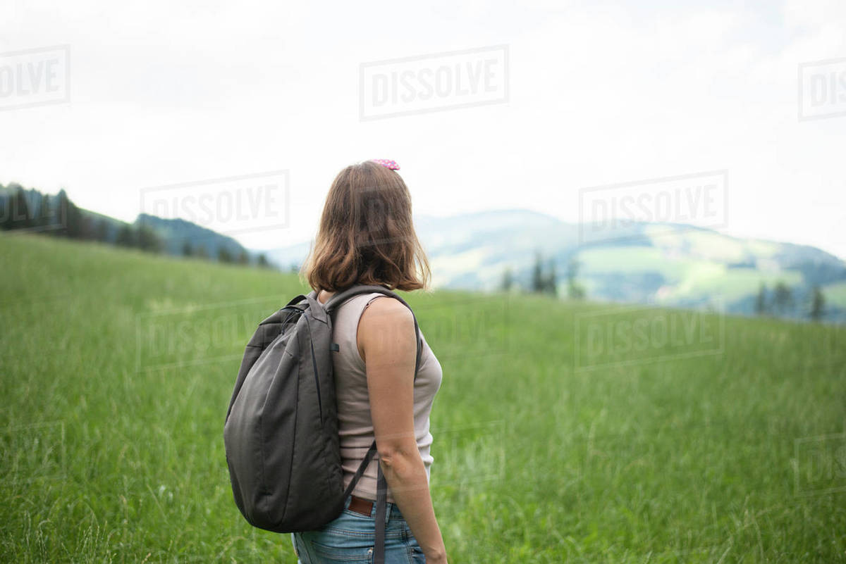 Back view of woman with backpack standing in field  Royalty-free stock photo