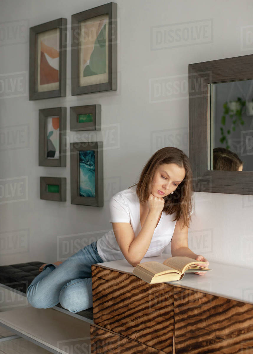 Woman sitting and reading a book at home Royalty-free stock photo