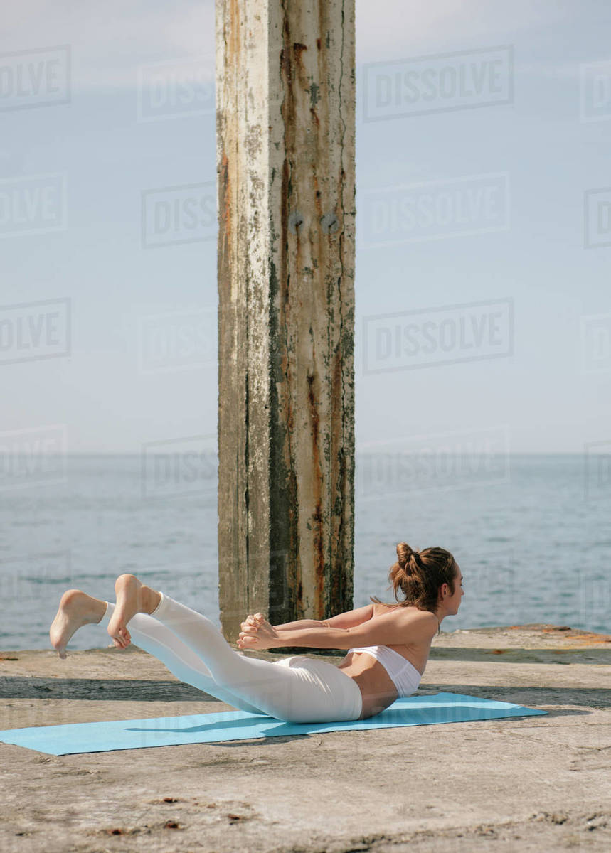 Woman practicing yoga at seaside during sunny day. Woman lying down on yoga mat doing yoga exercise Royalty-free stock photo