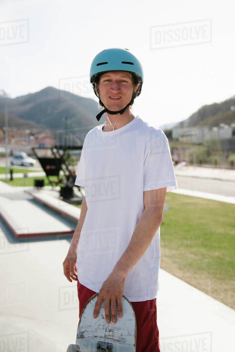 Young man carrying skateboard looking at camera Royalty-free stock photo