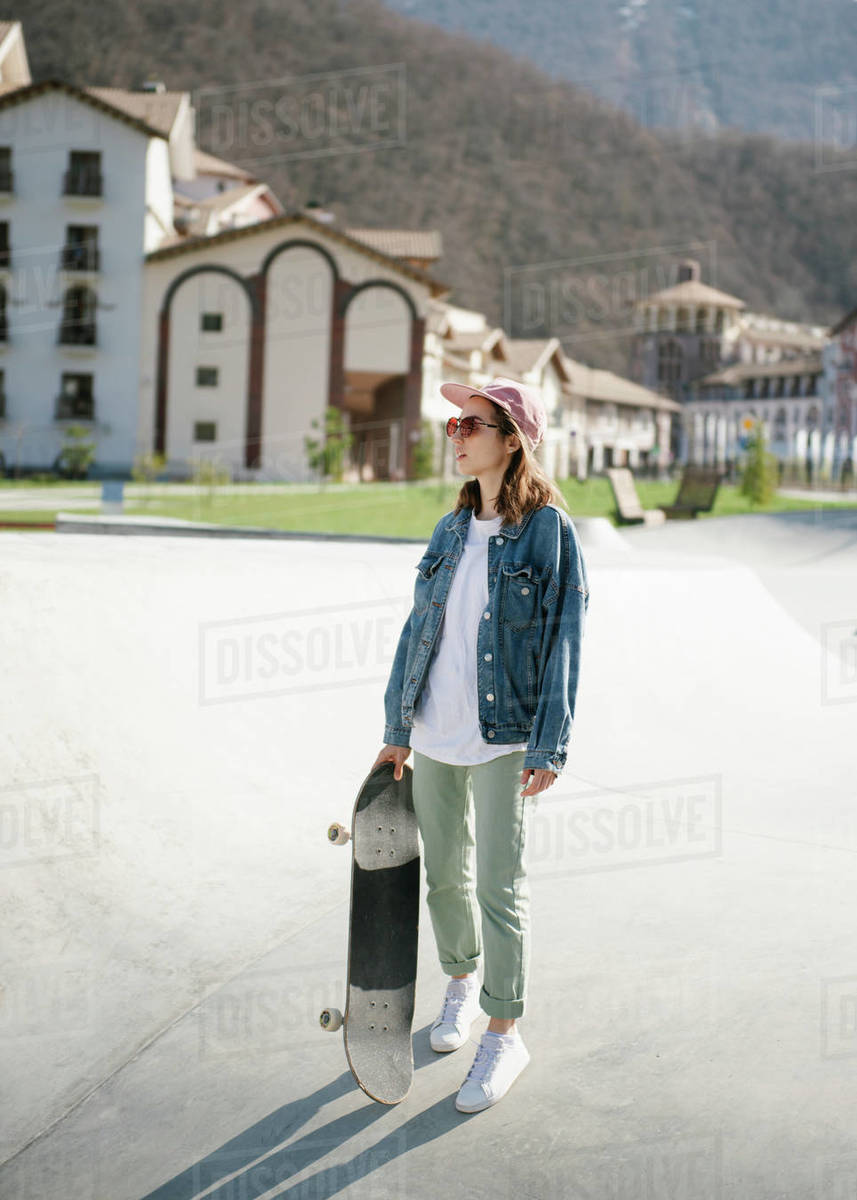 Young woman carrying skateboard looking away outdoor Royalty-free stock photo
