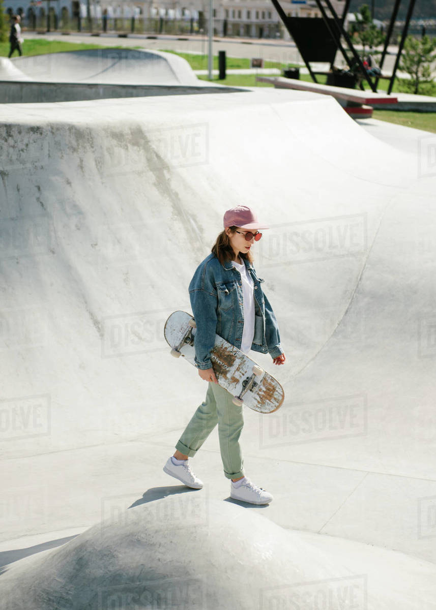 Young woman carrying skateboard outdoor Royalty-free stock photo
