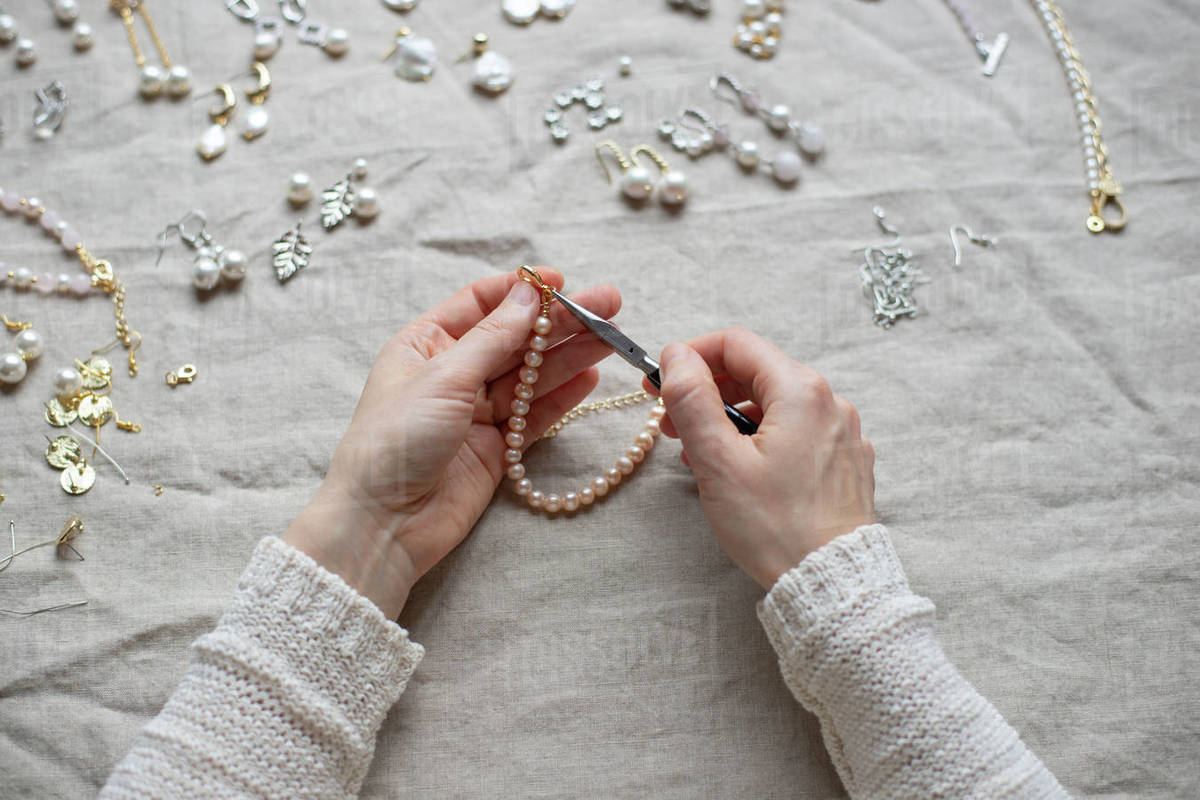 Jewelry designer working in studio with tools making pearl bracelet Royalty-free stock photo