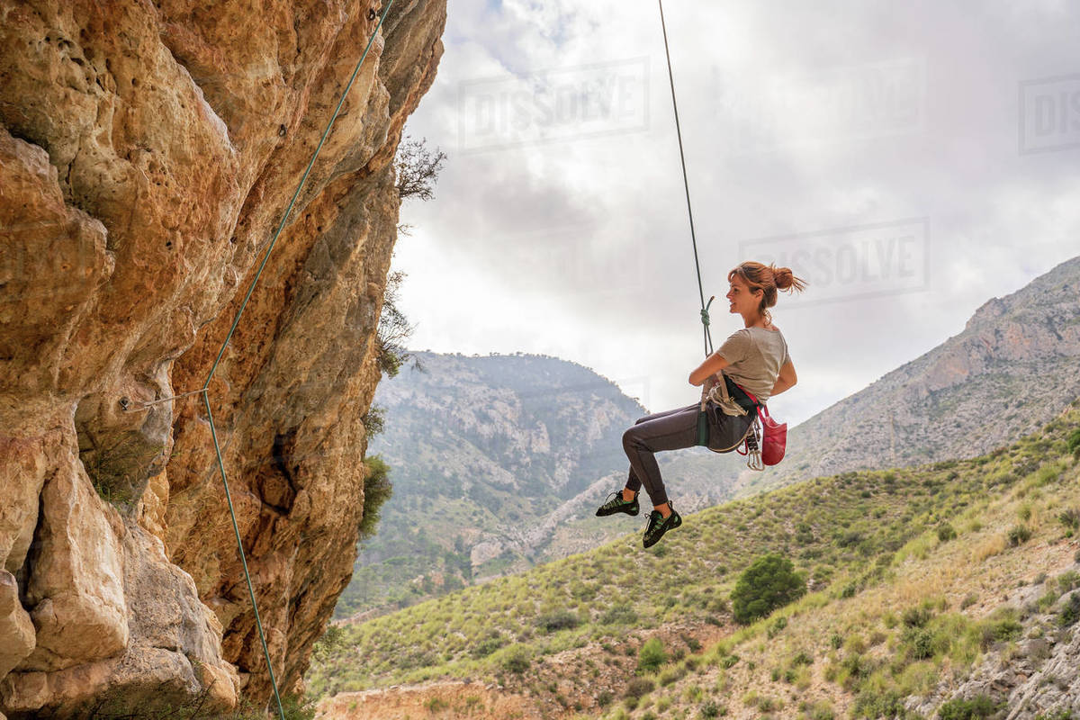 From below athletic female alpinist hanging on cliff under cloudy sky Royalty-free stock photo