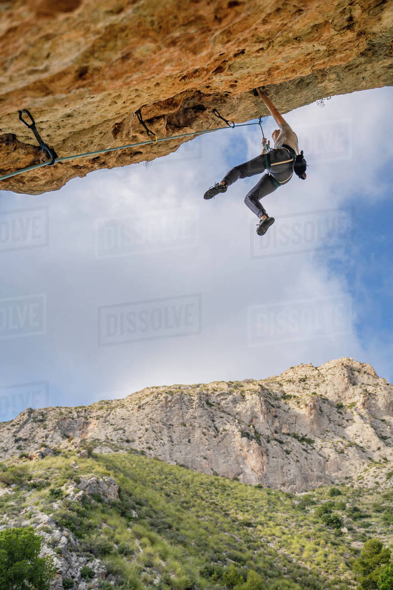 From below faceless professional alpinist climbing down from cliff under cloudy sky in summer day Royalty-free stock photo
