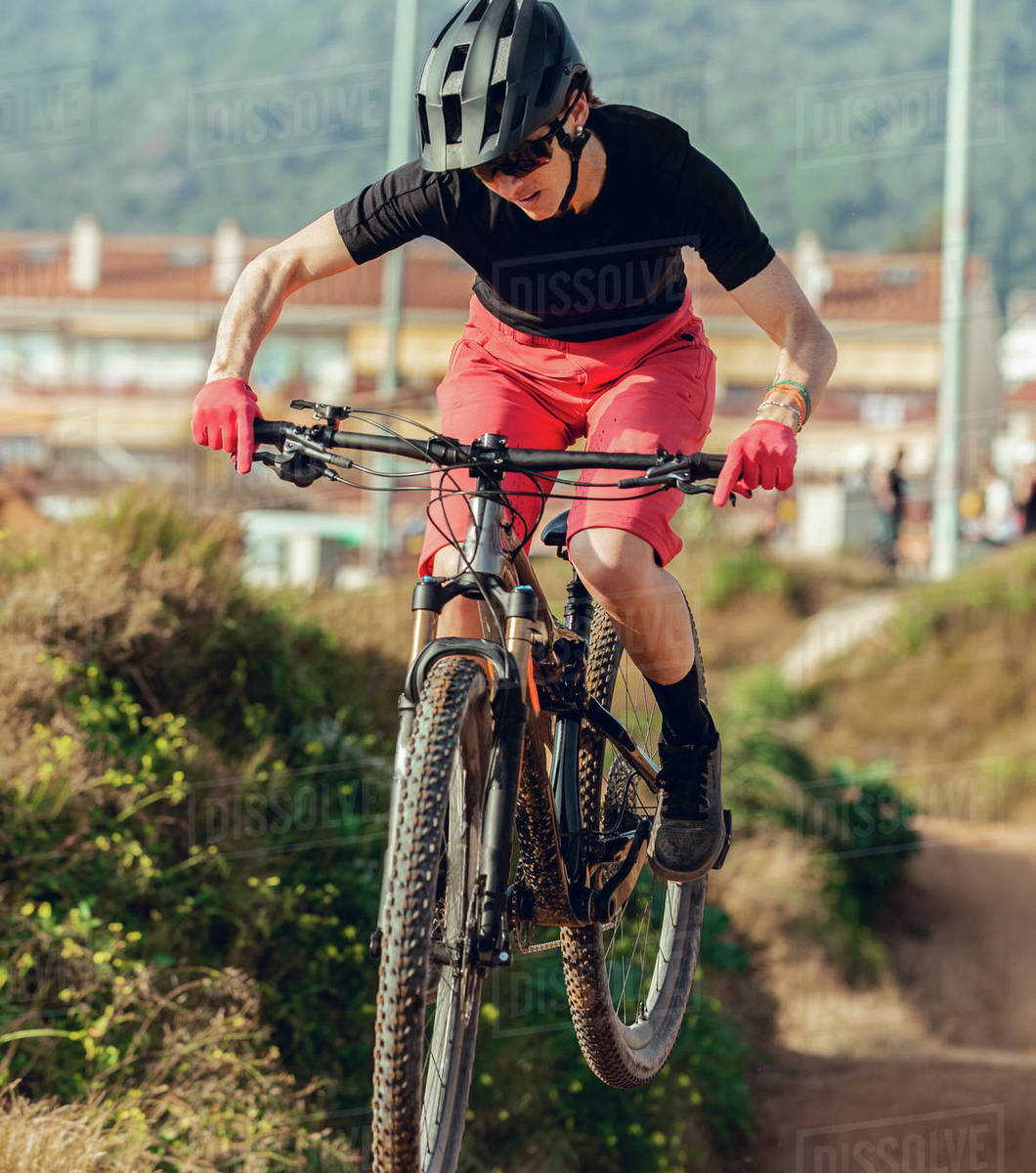 Sportswoman in black helmet and red sportswear with glasses riding mountain bike jumping in training track Royalty-free stock photo