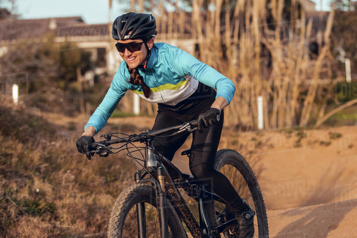 Sportswoman in black helmet and blue sportswear with glasses riding mountain bike on training track Royalty-free stock photo