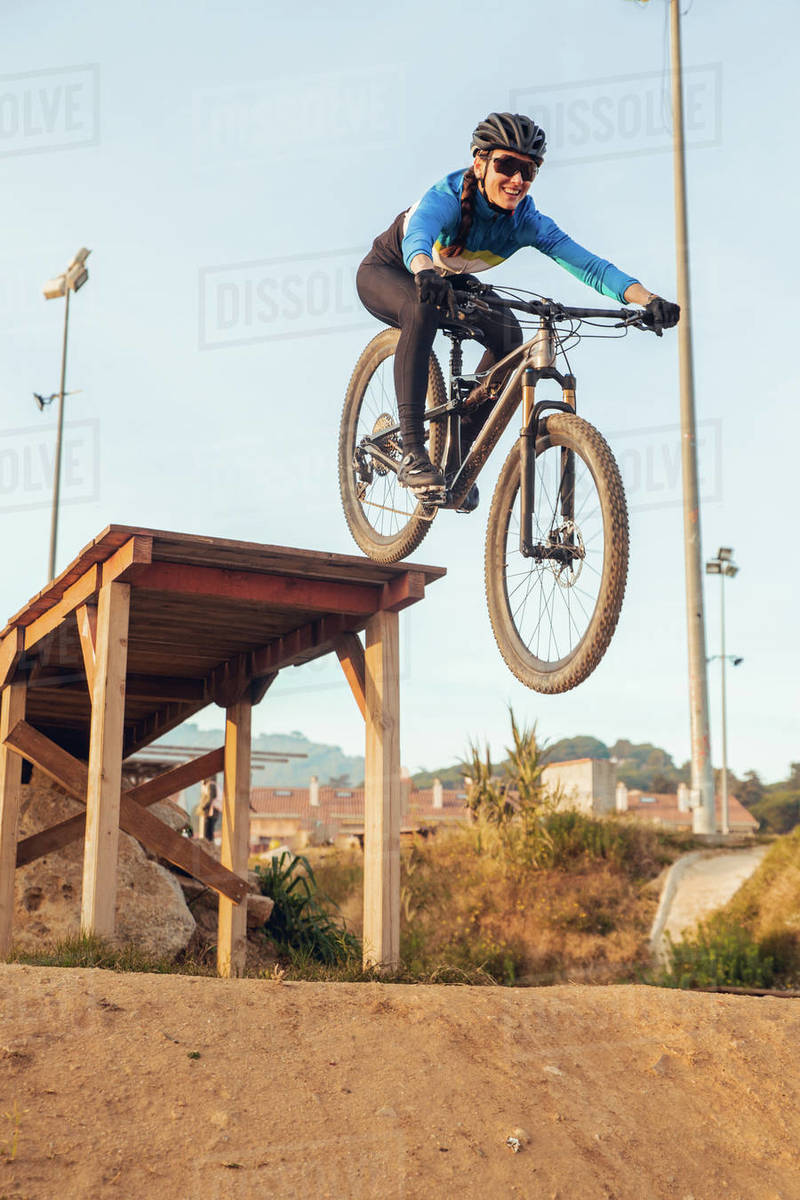 Sportswoman in black helmet and sportswear with glasses riding mountain bike jumping in training track Royalty-free stock photo