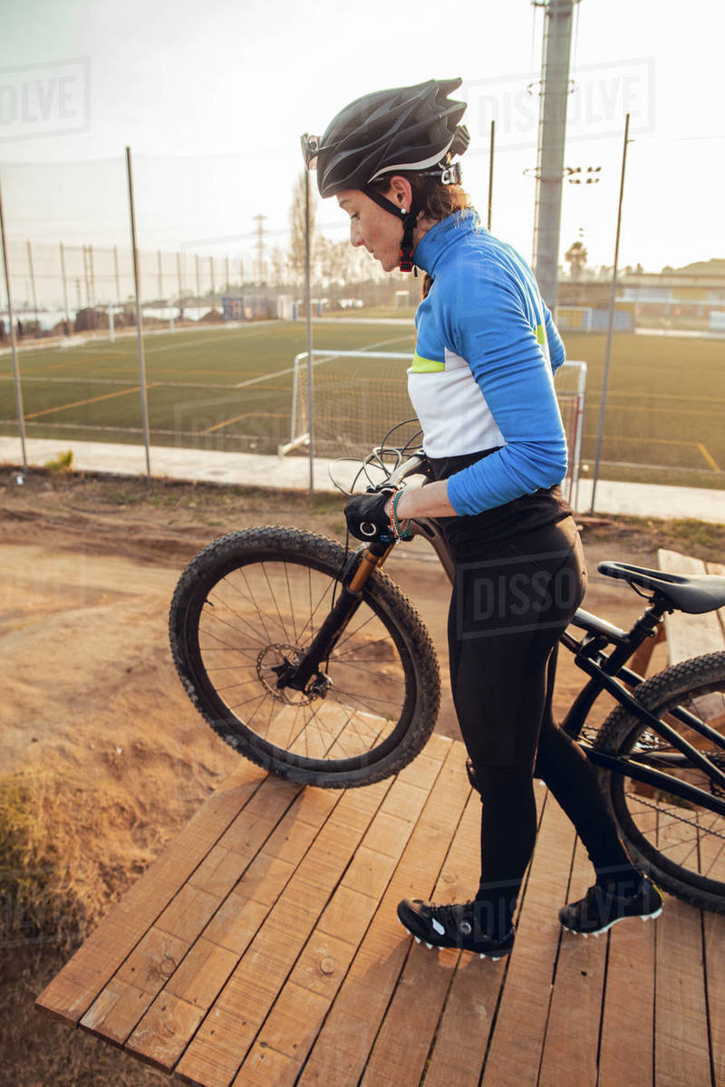 Young female in sportswear and helmet standing on wooden platform with dusty mountain bike smiling and looking down Royalty-free stock photo
