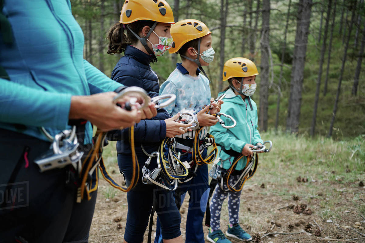 Group of children in masks and helmets preparing carabiners of safety harness while standing near crop female instructor in adventure time in forest Royalty-free stock photo