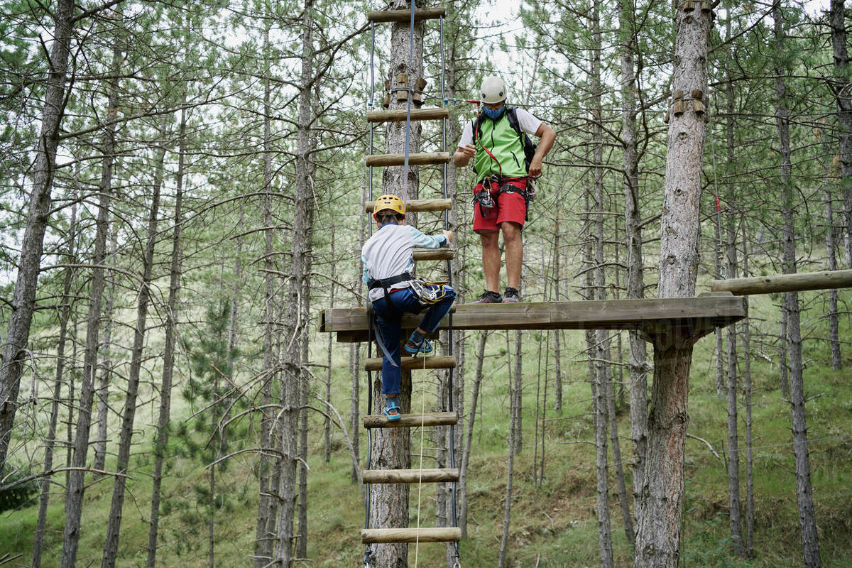 Unrecognizable kid climbing ladder near male instructor standing on platform while spending time in adventure park together Royalty-free stock photo